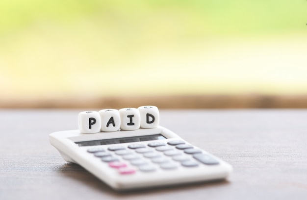Palavras pagas e calculadora na mesa para pagamento de tempo pago no negócio de escritório