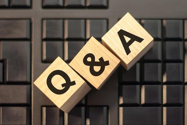 Palavras: q e a em letras do alfabeto de madeira 3d em uma parede de teclado com espaço de cópia, conceito de negócio. q e a - abreviação de pergunta e resposta.