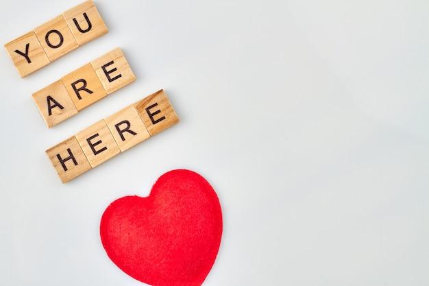 Palavras ternas de amor. o coração vermelho representa sentimentos. blocos do alfabeto com letras isoladas no fundo branco.
