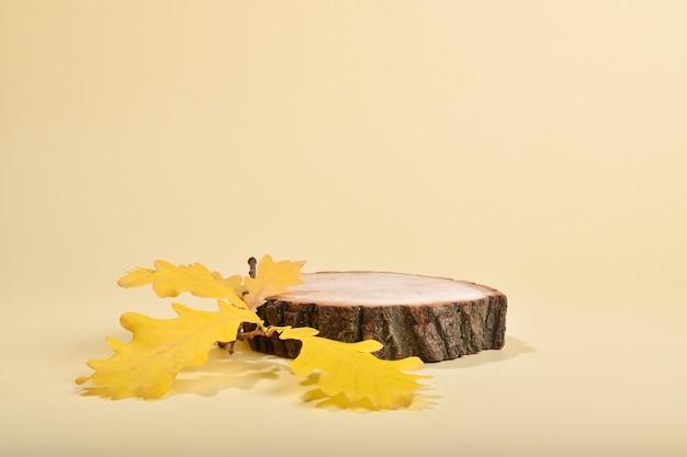 Palco com montra em madeira natural e folhas de carvalho. o pódio de outono para a apresentação de produtos e cosméticos é feito de uma barra cilíndrica sobre fundo bege.