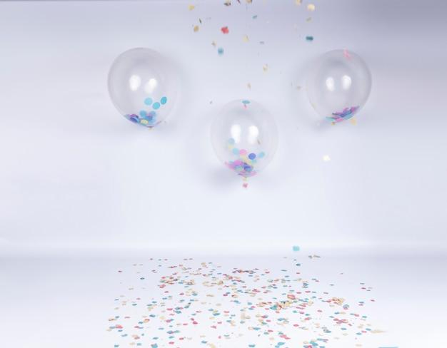 Palco de comemoração de aniversário com balões transparentes e confetes