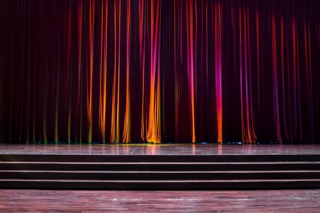 Palco de madeira e cortinas vermelhas.