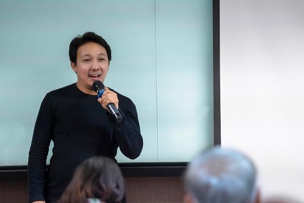 Palestrante asiático ou palestra com terno casual no palco em frente à apresentação da sala