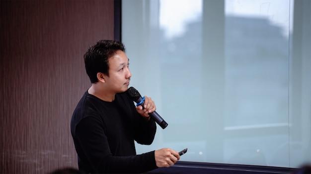 Palestrante asiático ou palestra com traje casual no palco em frente ao salão
