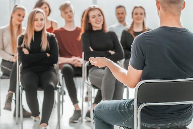 Palestrante e um grupo de jovens sentados em uma sala de conferências