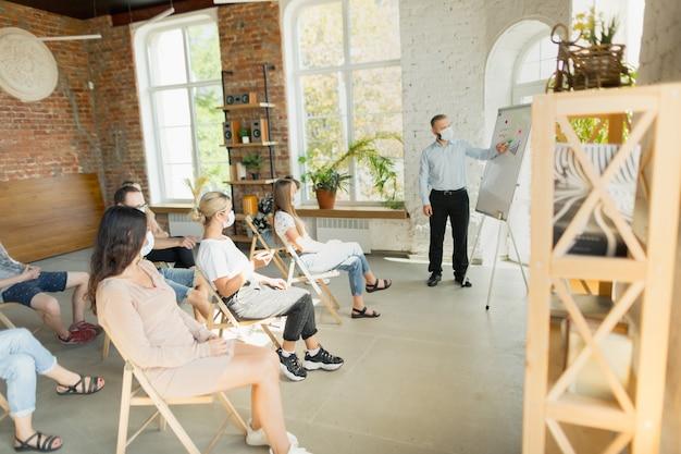 Palestrante masculino fazendo apresentação no salão da audiência do workshop da universidade ou sala de conferência