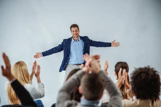 Palestrante motivacional sorridente em frente ao público que está batendo palmas.