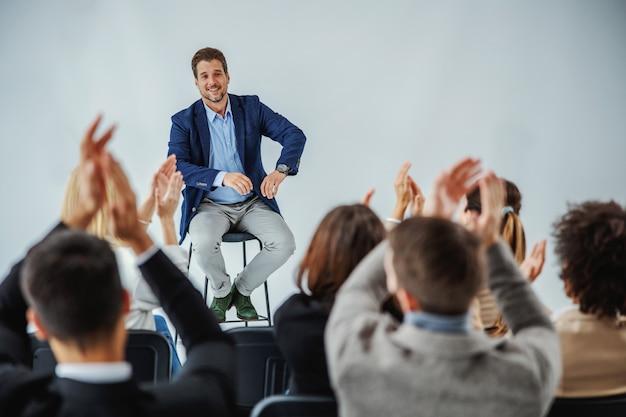 Palestrante motivacional sorridente, sentado na frente de seu público, que está batendo palmas.