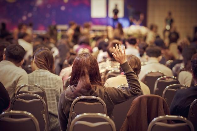 Palestrante no palco com vista traseira do público