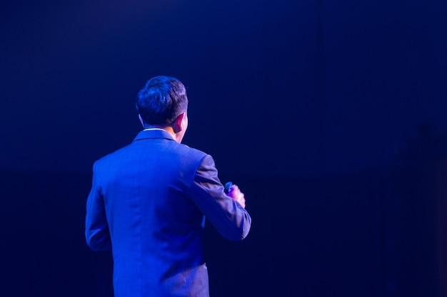 Palestrante no palco e dando palestra na reunião de negócios. audiência na sala de conferências. negócios e empreendedorismo.