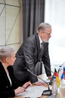 Palestrante sênior e confiante em um elegante terno cinza explicando sua opinião aos sócios, outros executivos em reunião multiétnica no escritório, usando microfones para fazer um discurso