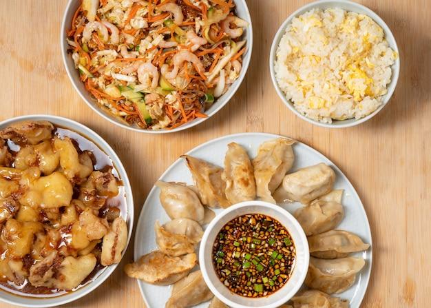 Paleta colorida de salada de camarão com comida asiática para viagem, frango crocante e doce, arroz e bolinhos fritos na madeira