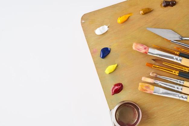 Paleta com tintas e pincéis para pintura a óleo em fundo branco