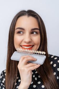 Paleta com tons de dentes. amostras dentais de dentes tingidos. menina com lábios vermelhos escolhe a cor perfeita dos dentes. fechar-se.