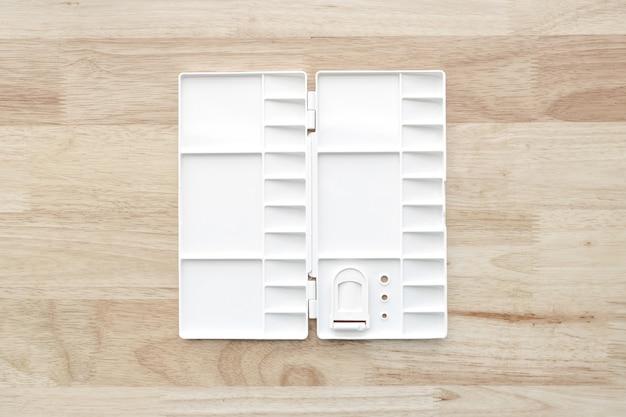 Paleta de aquarela branca. bandeja de aquarela vazia isolada em fundo de madeira. paleta de tinta plástica branca.