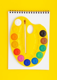 Paleta de aquarela no scetchbook sobre fundo amarelo. conceito de desenho.