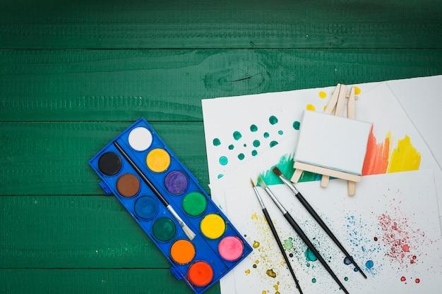 Paleta de aquarela; pincéis de pintura; mini cavalete e papel de mão desenhada sobre a mesa verde