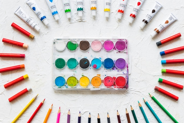 Paleta de aquarela rodeada por material de pintura