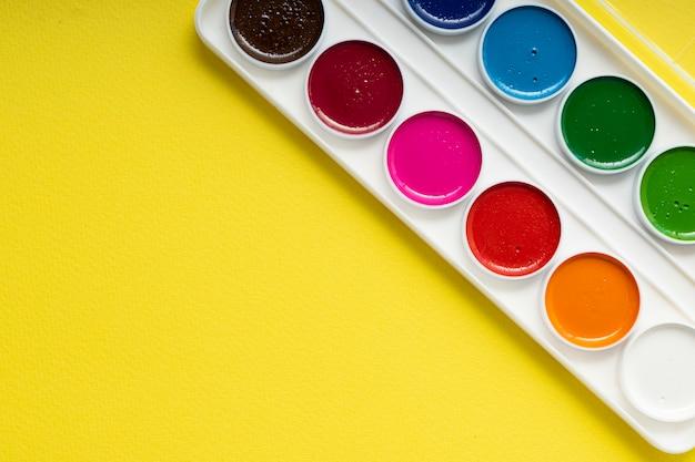 Paleta de aquarelas em um fundo amarelo