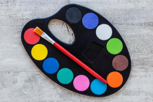 Paleta de bandeja de artista multicolorida em fundo de madeira