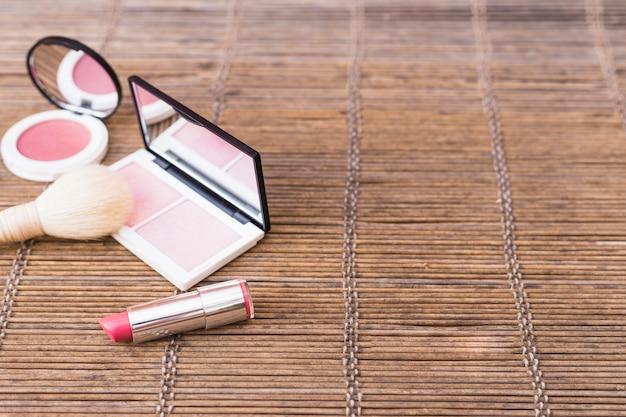 Paleta de blush cor-de-rosa; pincel de maquiagem e batom no placemat