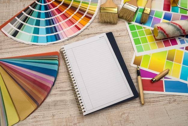 Paleta de cores com ferramentas de pintura e bloco de notas vazio para design Foto Premium