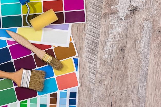 Paleta de cores com ferramentas de pintura na mesa de madeira