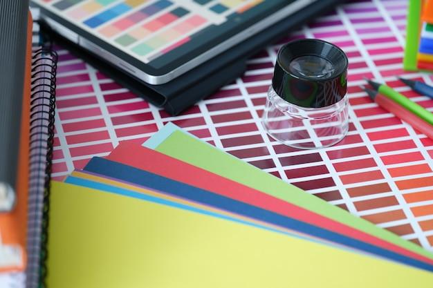 Paleta de cores com papel colorido e tablet com amostras de cores na mesa de seleção de cores
