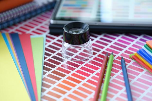 Paleta de cores com tons de rosa de lápis e papel colorido mentem sobre a mesa. escolhendo o tom certo de conceito de cor