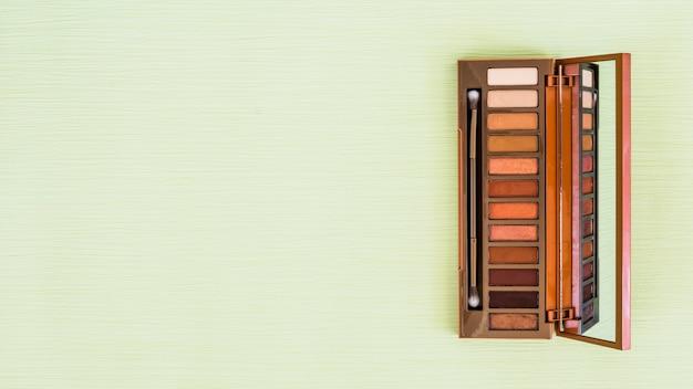 Paleta de madeira da sombra com espelho e pincel de maquiagem em pano de fundo verde hortelã