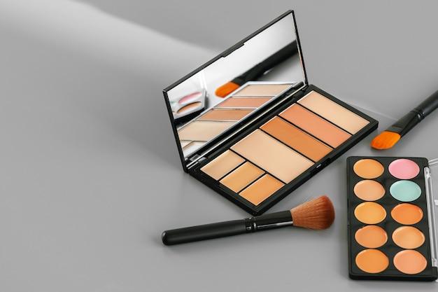 Paleta de maquiagem com corretivo colorido em fundo cinza