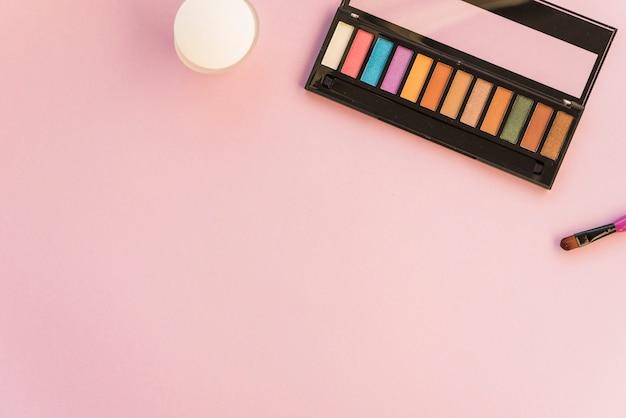 Paleta de maquiagem com pincel sobre fundo colorido