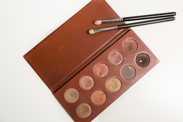 Paleta de maquiagem profissional nas cores bronze com pincéis em um fundo branco
