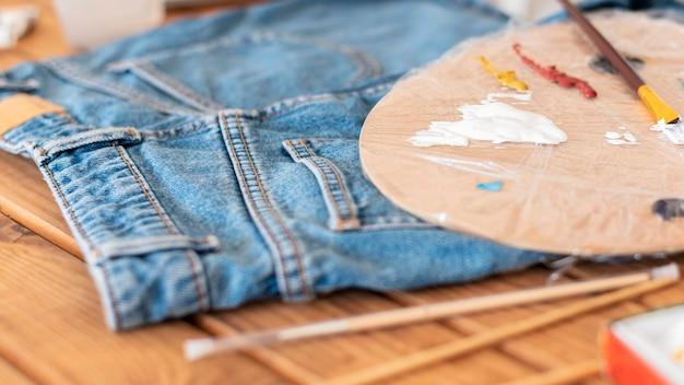 Paleta de pintura de ângulo alto e jeans