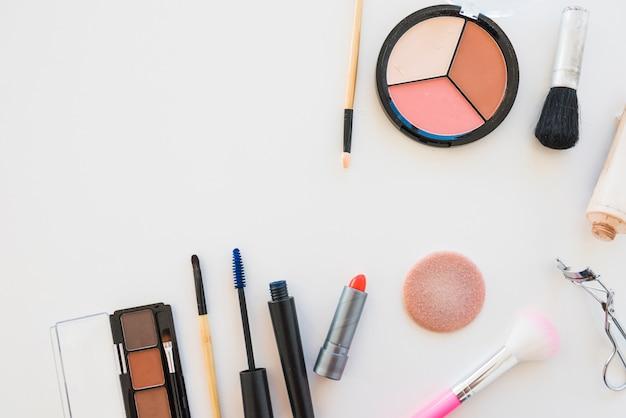 Paleta de sombra de maquiagem; escova; esponja; batom; rímel em fundo branco