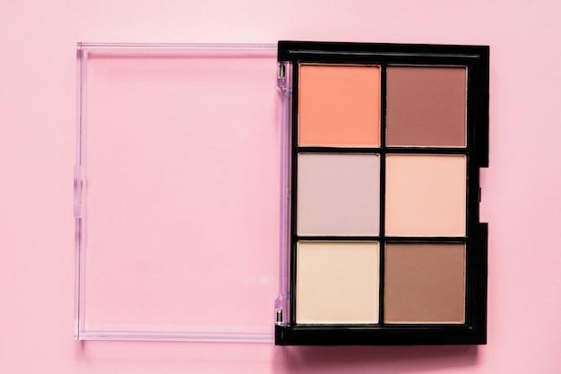 Paleta de sombras em tons de marrons e roxos em fundo rosa