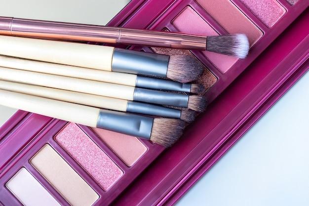 Paleta de sombras em tons de rosa e um conjunto de pincéis de maquiagem
