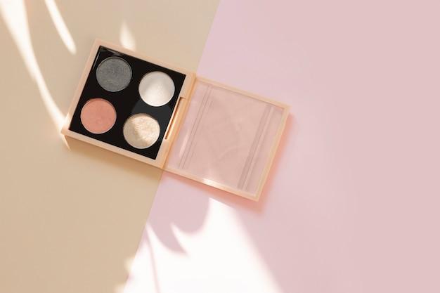 Paleta de sombras para os olhos em um bloco de cor de fundo bege e rosa pastel com uma sombra de folha monstera com copyspace