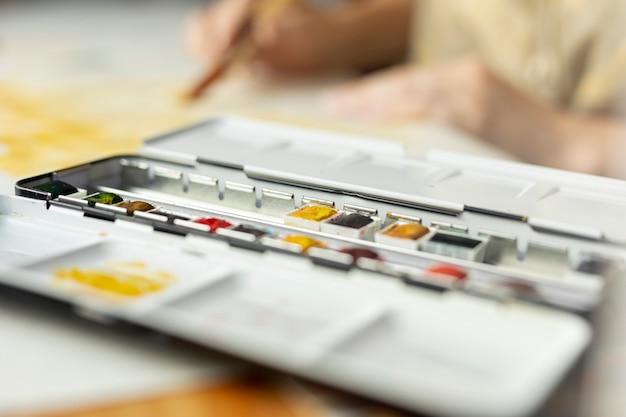 Paleta de tintas de close-up com a pessoa borrada