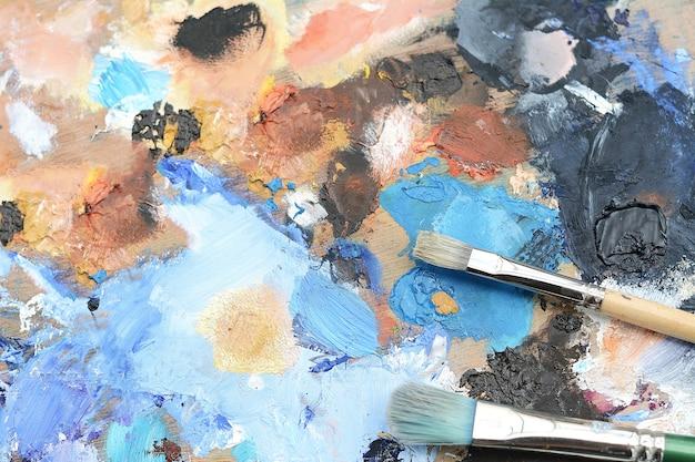 Paleta do artista colorido com traços de tinta a óleo.