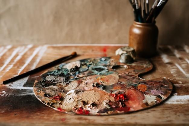 Paleta do artista com tintas a óleo e pincéis.