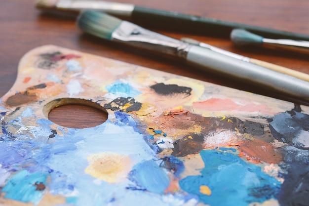 Paleta do artista com traços de tinta a óleo colorido e pincéis