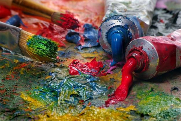 Paleta do artista, tubos e pincéis close-up