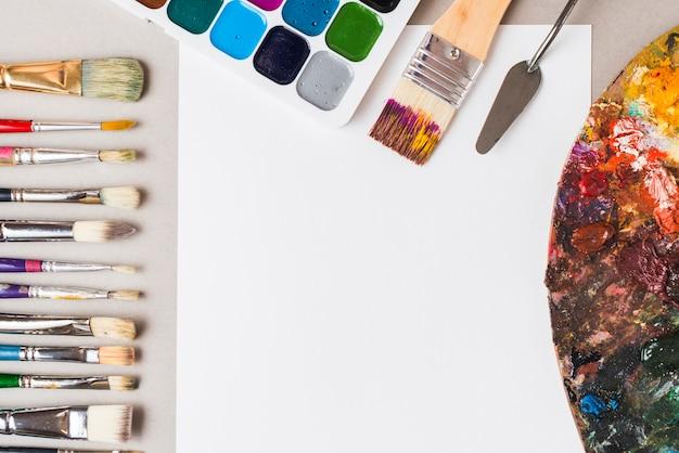 Paleta e ferramentas de pintura perto de papel