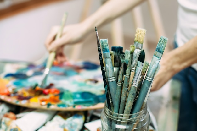 Paleta, pincéis, tintas, foco seletivo em primeiro plano. imagem de fundo.