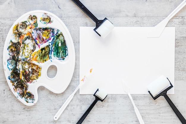 Paletas de artistas multicoloridas e pincéis brancos