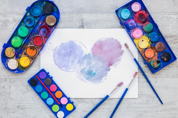 Paletas de artistas multicoloridas em recipientes azuis