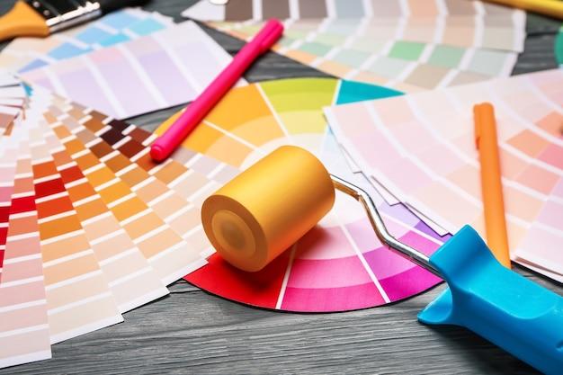 Paletas de cores com rolo de pintura na mesa de madeira