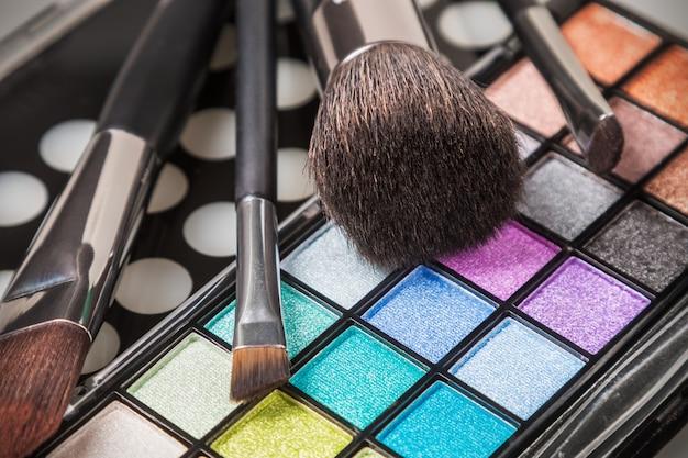 Paletas de sombras de maquiagem coloridas com pincéis de maquiagem