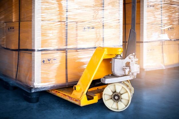 Paleteira manual com caixas de embalagem filme plástico embrulhado em caixas de transporte de carga de paletes